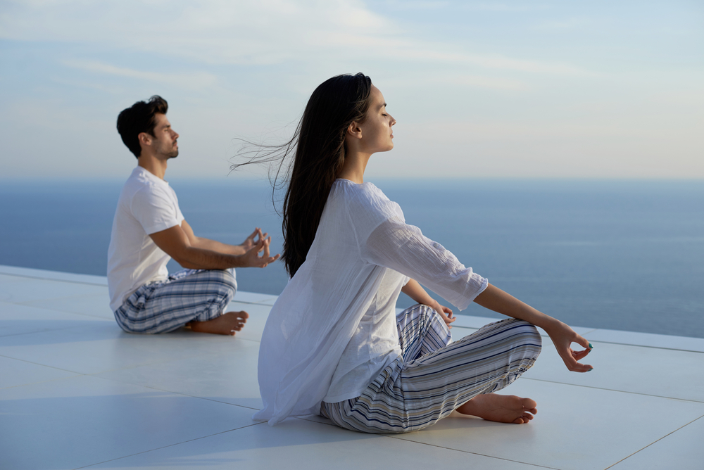 young couple practicing yoga at sunset in modern home terace with ocean and sunset in background-3